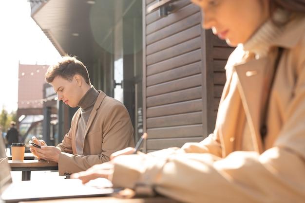 Zijaanzicht van een elegante jongeman in jas en trui die in smartphone scrolt terwijl hij op het terras zit en iets drinkt
