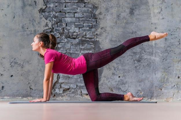 Zijaanzicht van een fitness jonge vrouw die de oefening van de ezelsschop tegen muur doet