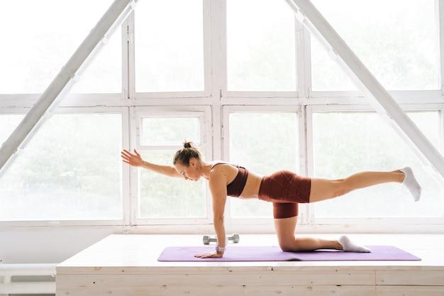 Zijaanzicht van een fitte jonge vrouw met een perfect atletisch lichaam die sportkleding draagt die rekoefeningen doet op de vensterbank tijdens de training. concept van gezonde levensstijl en fysieke activiteit thuis