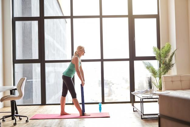 Zijaanzicht van een fitte volwassen vrouw die traint met behulp van een weerstandsband die online videoklassen uitzendt op een