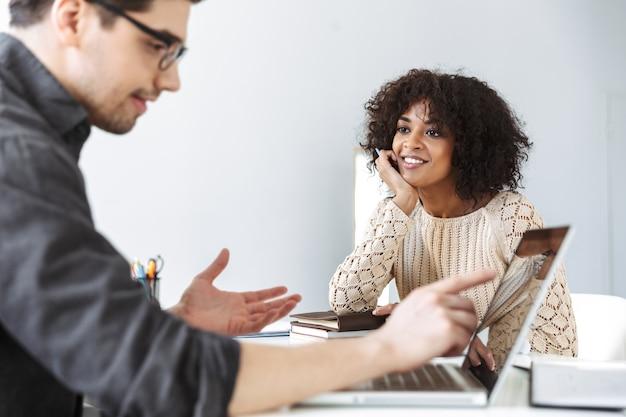 Zijaanzicht van een geconcentreerde man in een bril die zit op een ontmoeting met zijn lachende collega op kantoor