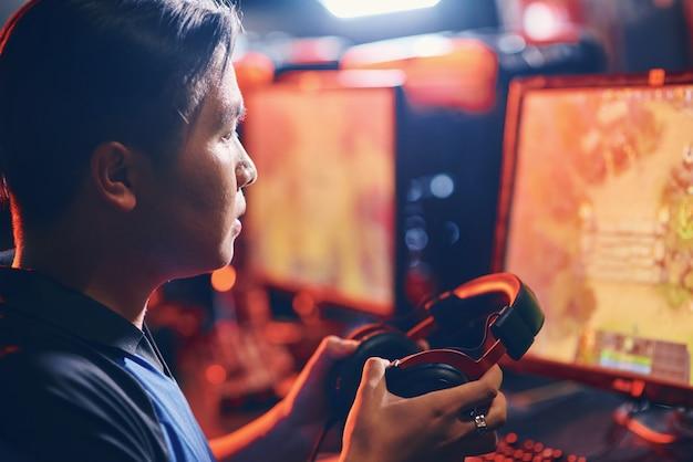 Zijaanzicht van een gefocuste aziatische man, mannelijke professionele cybersport-gamer die een koptelefoon vasthoudt en naar het pc-scherm kijkt tijdens het spelen van online videogames. deelnemen aan esport-toernooi