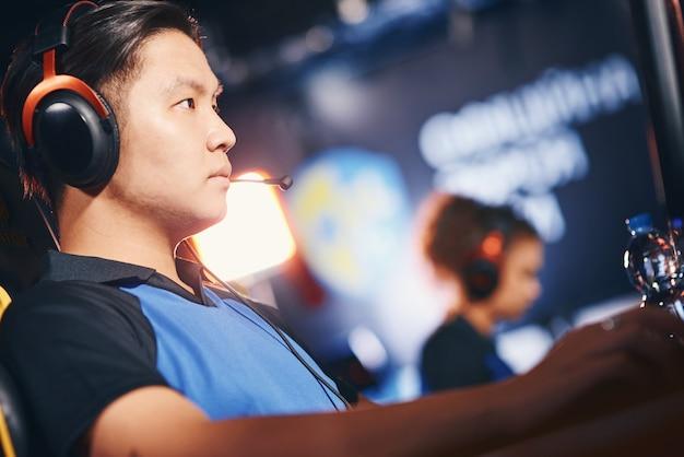 Zijaanzicht van een gefocuste aziatische mannelijke cybersport-gamer die een koptelefoon draagt die online speelt