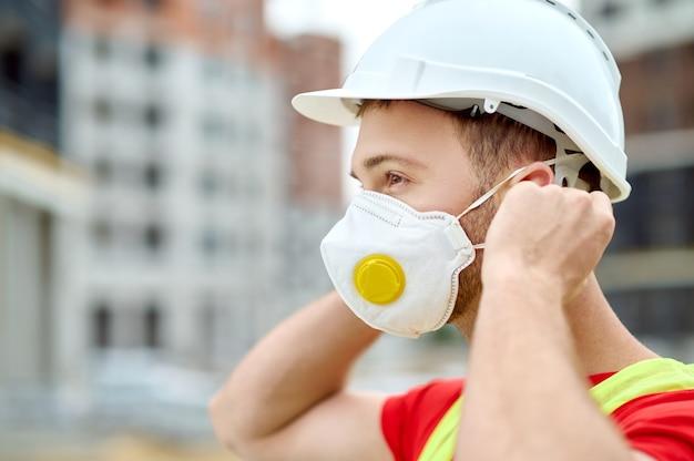 Zijaanzicht van een gefocuste donkerharige bebaarde bouwer in hoofddeksels die buiten een beschermend masker opzet