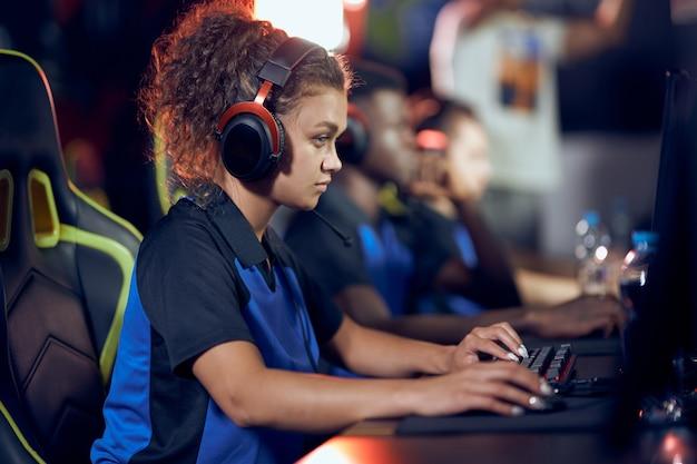 Zijaanzicht van een gefocuste vrouwelijke cybersport-gamer van gemengd ras die een koptelefoon draagt die online speelt
