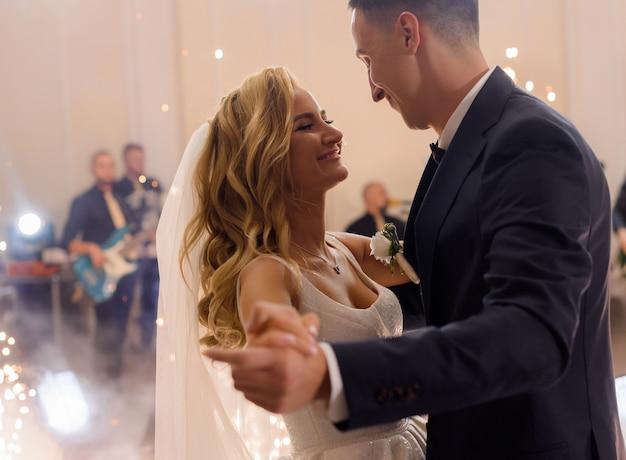 Zijaanzicht van een geglimlacht jong getrouwd stel, dat hun huwelijk viert, handen vasthoudt en danst