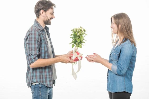 Zijaanzicht van een gelukkig man cadeau en bloem te geven aan zijn vriendin op witte achtergrond