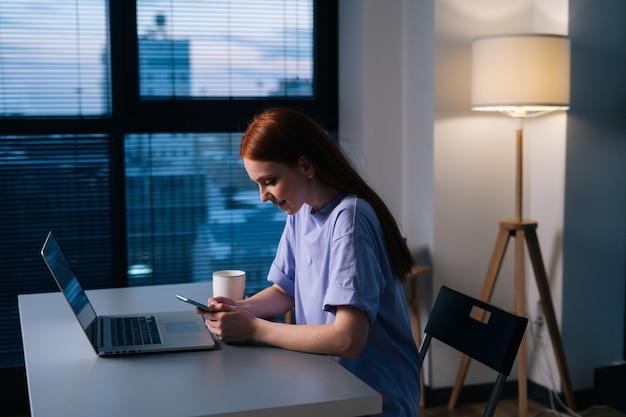 Zijaanzicht van een gelukkige jonge vrouw die een mobiele telefoon gebruikt die aan het bureau zit met een laptop in de buurt van het raam met stadsgezichtavond laat.
