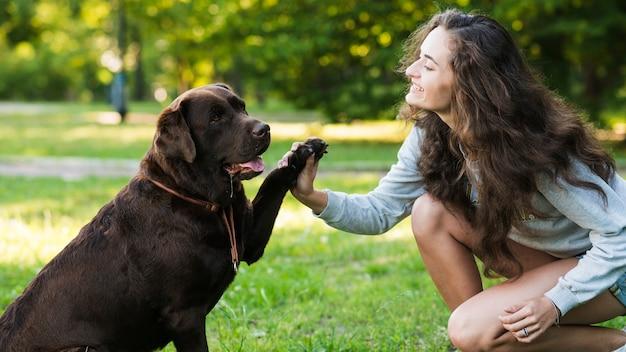 Zijaanzicht van een gelukkige vrouw die met haar hond speelt