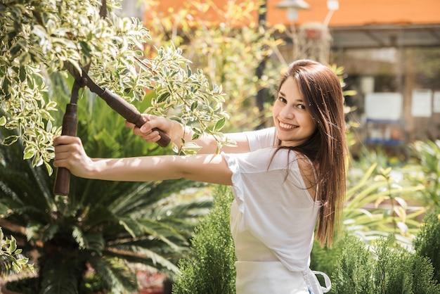 Zijaanzicht van een gelukkige vrouw scherpe bladeren met tuinieren schaar