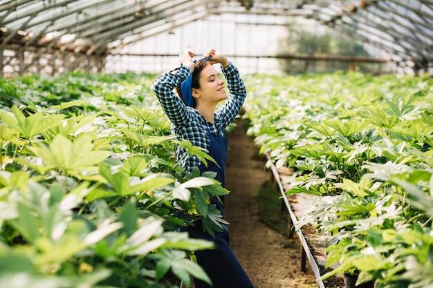 Zijaanzicht van een gelukkige vrouwelijke tuinman die zich in serre bevindt