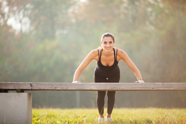 Zijaanzicht van een gemotiveerde aziatische, portret van mooie sportieve vrouw 20s in sportkleding doet push-ups en luistert naar muziek met bluetooth-oordopjes tijdens training in groen park
