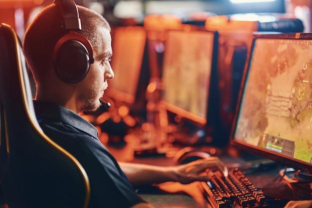 Zijaanzicht van een gerichte mannelijke professionele cybersport-gamer die een koptelefoon draagt en naar het pc-scherm kijkt