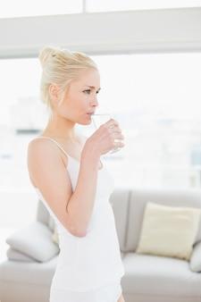 Zijaanzicht van een geschikt vrouwen drinkwater bij de gymnastiek