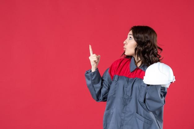 Zijaanzicht van een geschokte vrouwelijke architect die een helm vasthoudt en omhoog wijst op een geïsoleerde rode achtergrond