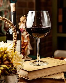 Zijaanzicht van een glas rode wijn op boek