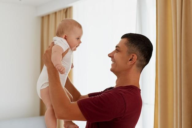 Zijaanzicht van een glimlachende gelukkige vader die bij het raam in een lichte woonkamer staat en zijn dochtertje of zoon vasthoudt, een man die tijd doorbrengt, thuis met de baby speelt.