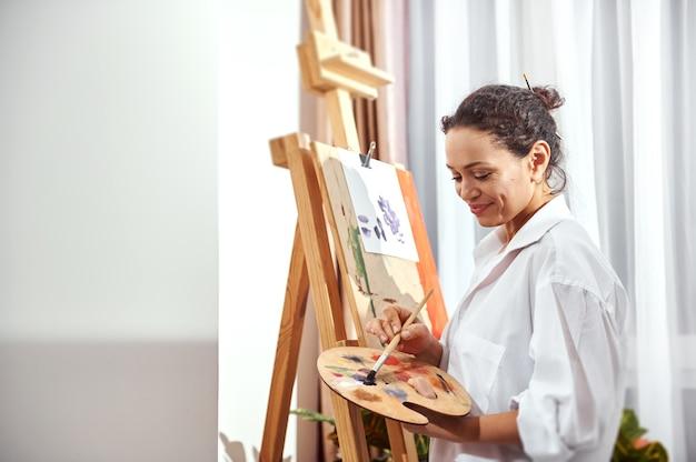 Zijaanzicht van een glimlachende gelukkige vrouwelijke schilder die olieverf op een palet mengt en zich voor een ezel bevindt