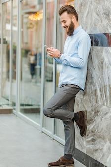 Zijaanzicht van een glimlachende jonge mens die cellphone gebruikt