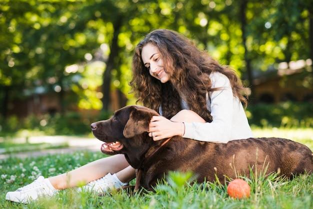 Zijaanzicht van een glimlachende jonge vrouw die haar hond in tuin strijken