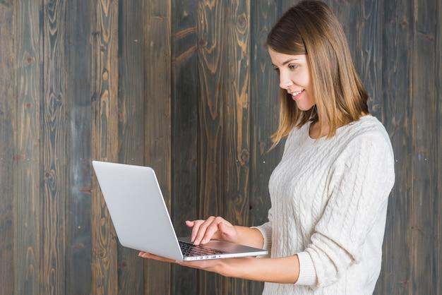 Zijaanzicht van een glimlachende jonge vrouw die laptop met behulp van tegen houten muur