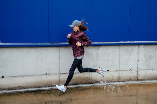 Zijaanzicht van een glimlachende jonge vrouw die op de straat loopt. stadsleven.