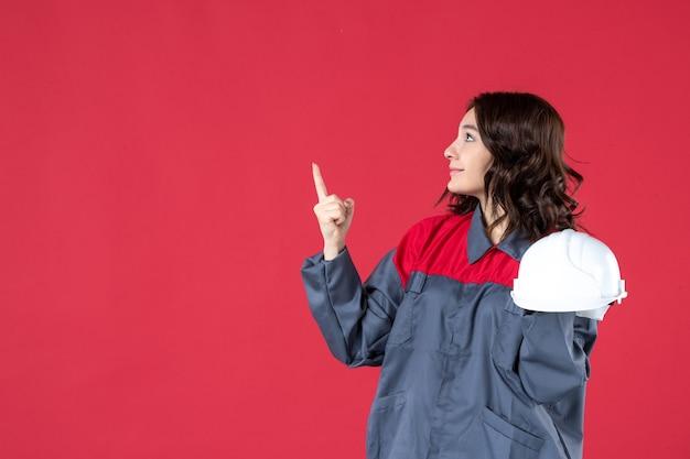 Zijaanzicht van een glimlachende vrouwelijke architect die een helm vasthoudt en omhoog wijst op een geïsoleerde rode achtergrond