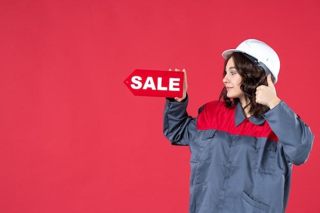 Zijaanzicht van een glimlachende vrouwelijke werknemer in uniform met een helm en wijzend verkooppictogram dat een goed gebaar maakt op geïsoleerde rode achtergrond