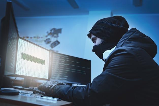 Zijaanzicht van een hacker die vanuit zijn ondergrondse schuilplaats bedrijfsgegevensservers hackt. de plaats heeft een donkere sfeer, veel displays?
