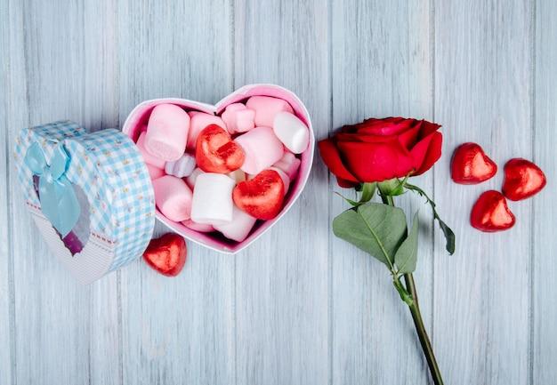 Zijaanzicht van een hartvormige geschenkdoos gevuld met roze marshmallow en chocolade snoepjes verpakt in rode folie en rood roze bloem op grijze houten tafel