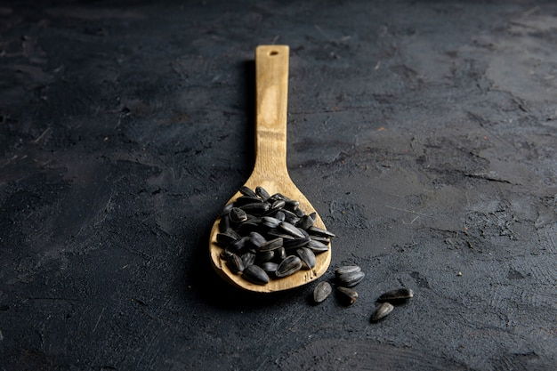 Zijaanzicht van een houten lepel met zwarte zonnebloempitten op zwart