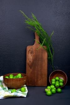Zijaanzicht van een houten snijplank met venkel en zure groene pruimen in houten kommen op zwarte tafel