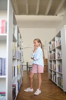 Zijaanzicht van een jong meisje met een verbaasde blik op haar gezicht dat voor boekenplanken in de bibliotheek staat