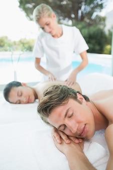 Zijaanzicht van een jong paar die van massage genieten bij gezondheidslandbouwbedrijf