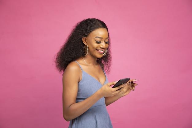 Zijaanzicht van een jonge afrikaanse vrouw die online winkelt met haar smartphone en creditcard