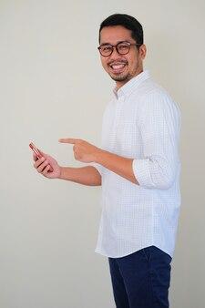 Zijaanzicht van een jonge aziatische zakenman die gelukkig glimlacht terwijl hij met zijn vinger naar zijn smartphone wijst