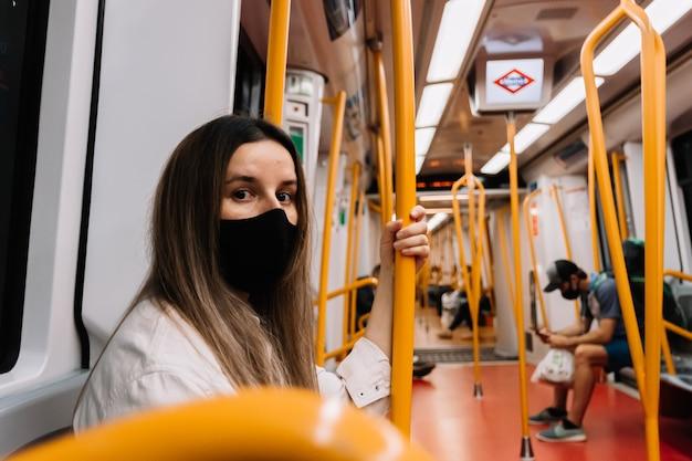 Zijaanzicht van een jonge blonde vrouw met een gezichtsmasker die in een metro in de stad madrid zit.