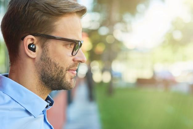 Zijaanzicht van een jonge knappe zakenman die naar muziek luistert met draadloze oortelefoons