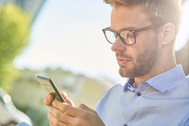 Zijaanzicht van een jonge knappe zakenman die smartphone gebruikt terwijl hij buiten op de bank zit op een