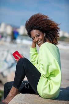 Zijaanzicht van een jonge krullende afro vrouw zittend op golfbreker rotsen genieten en glimlachen tijdens het gebruik van een mobiele telefoon om muziek te luisteren op een zonnige dag
