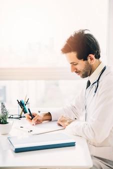 Zijaanzicht van een jonge mannelijke arts die op klembord in kliniek schrijft
