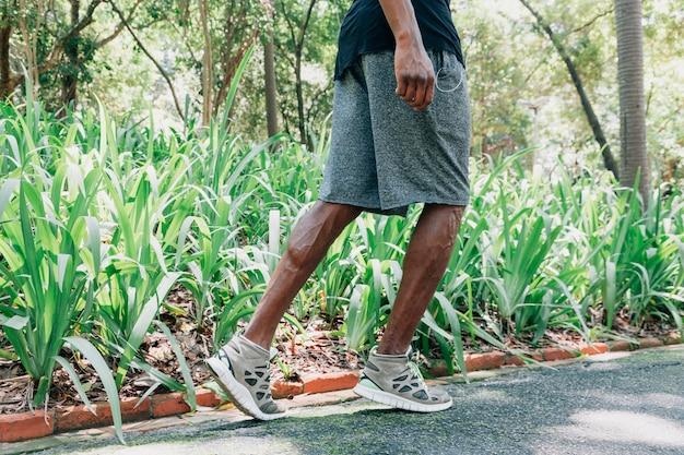 Zijaanzicht van een jonge mannelijke atleet die in het park loopt