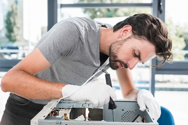 Zijaanzicht van een jonge mannelijke technicus die aan gebroken computer werkt