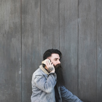 Zijaanzicht van een jonge mens het luisteren muziek op hoofdtelefoon tegen grijze houten muur