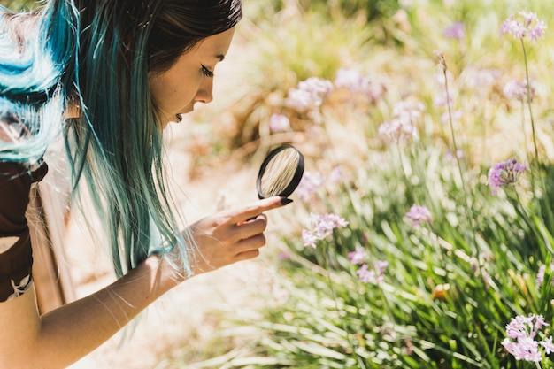 Zijaanzicht van een jonge moderne vrouw die bloemen door vergrootglas bekijkt