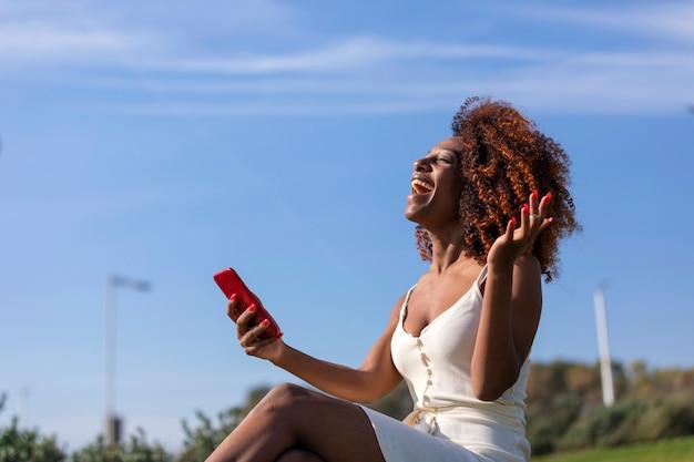Zijaanzicht van een jonge mooie krullende zitting van de afrovrouw op grond in een park en het gebruiken van een mobiele telefoon terwijl het glimlachen in een zonnige dag