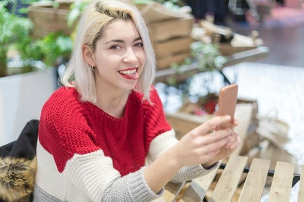 Zijaanzicht van een jonge mooie vrouw die een selfie in een bar neemt.