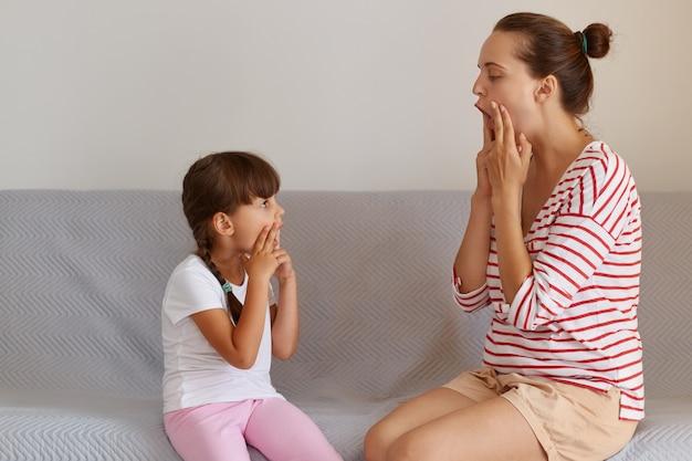 Zijaanzicht van een jonge volwassen blanke taaltherapeut die een klein kind de uitspraak leert, werkt aan spraakgebreken of problemen met een klein kindmeisje binnenshuis terwijl ze op de bank zit.