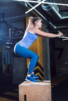 Zijaanzicht van een jonge vrouw die hurkende oefening op houten doos in gymnastiek doet