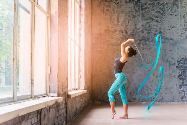 Zijaanzicht van een jonge vrouw die met blauw lint danst